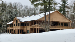 Photo of Founder's Lodge at Sky Lake. In this winter scene, we view the lodge from the lake side looking across the open field. The massive two story lodge is wrapped by balcony and windows facing the lake. Snow is in the foreground and on the roof. Out of photo.